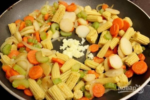 9. В последнюю очередь обжарьте до золотистого цвета лук. Добавьте на сковороду морковь с сельдереем, пропущенный через пресс чеснок и беби кукурузу (в данном случае добавлена также горсть водяного ореха).