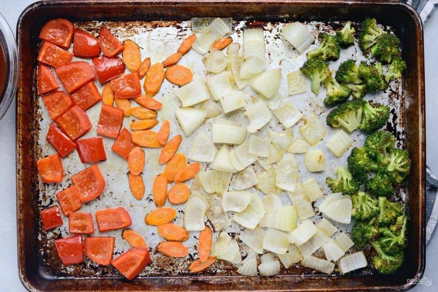 Тем временем нарежьте кружками морковь, лук и перец квадратиками, а брокколи разделите на соцветия. Сверху добавьте соль и масло. Отправьте запекаться овощи на 10 минут в духовку при 250 градусах.