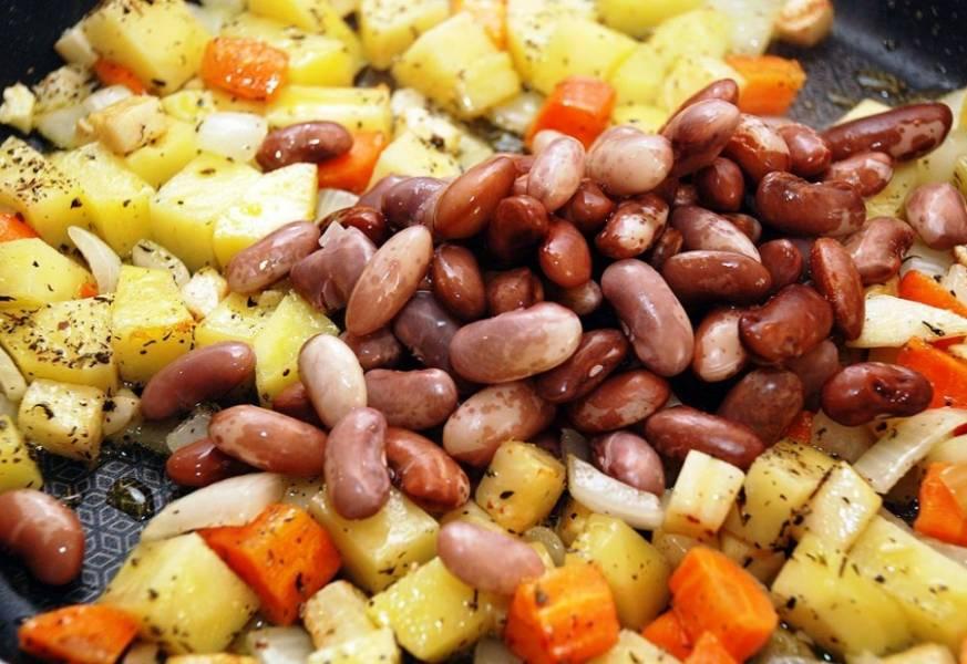 Затем добавьте фасоль, стакан горячей воды и доведите до кипения. Затем накройте крышкой и готовьте в течение 15 минут. Тем временем очистите помидоры от кожуры и семян и превратите в пюре, которое добавьте к остальным овощам. После этого готовьте блюдо еще 10 минут и подайте на стол в горячем виде – разогревания оно не терпит.