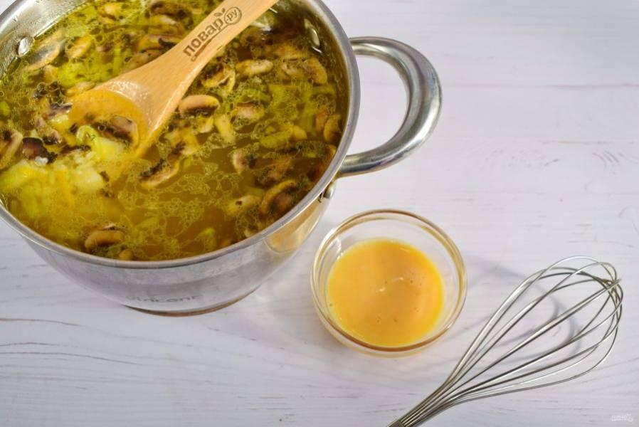 Грибы нарежьте тонкими ломтиками, обжарьте на разогретом масле до золотистой корочки. Отправьте с томатной зажаркой в суп. Яйца взбейте, влейте тонкой струйкой, помешивая. Добавьте соль и перец по вкусу.