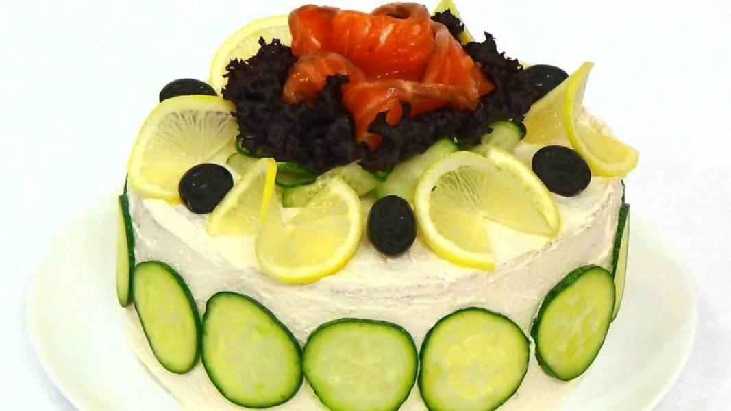 4. С помощью ножа для овощей нарежьте тонкие полоски огурца и украсьте торт. Добавьте ломтики лимона, листья салата, зелень, маслины и нарезанную рыбу. Приятного аппетита!