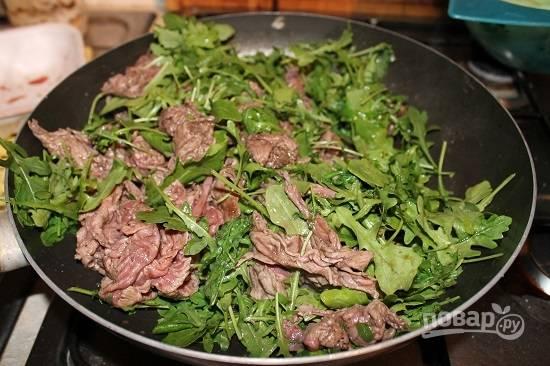 Добавим к мясу листья рукколы и через минуту уберем с огня.