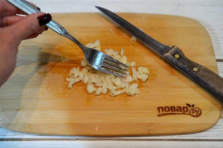 2. Добавьте к чесноку соль и разомните всё вилкой.