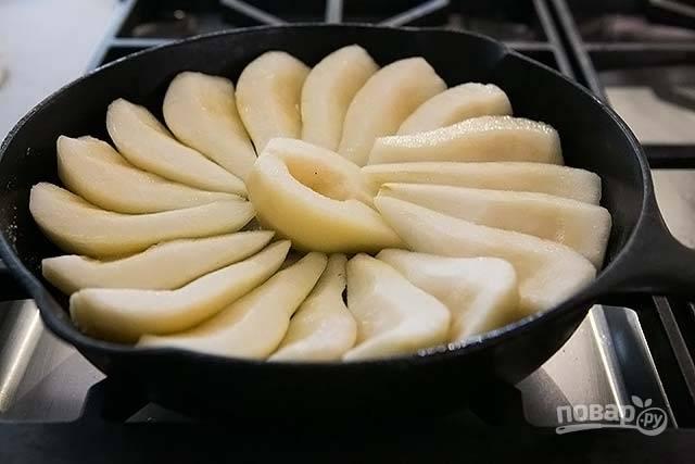 4.В сковороду к маслу и сахару выложите по центру половинку груши, остальные ломтики уложите по кругу плотно.