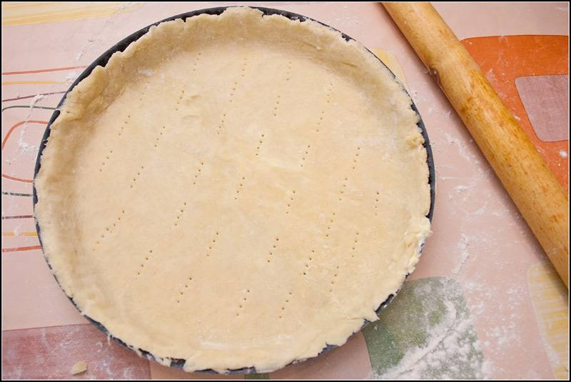 3. Выложить тесто в форму для запекания, сформировав бортики. Сделать небольшие проколы вилкой, накрыть пищевой пленкой и отправить в холодильник.