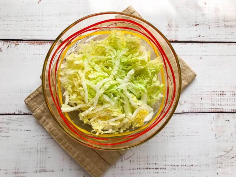 Пекинскую капусту мелко нарежьте и выложите в глубокую тарелку.