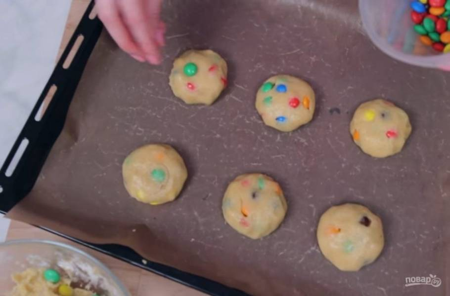 3. Смешайте сухие и жидкие ингредиенты. Добавьте конфеты и хорошо перемешайте. Смазанными растительным маслом руками сформируйте печенье, выложите его на застеленный пергаментной бумагой противень и сверху украсьте конфетами.