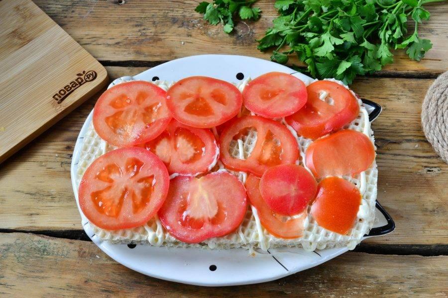 Снова накройте вафельным листом, смажьте майонезом и выложите тонкие кружочки помидора.