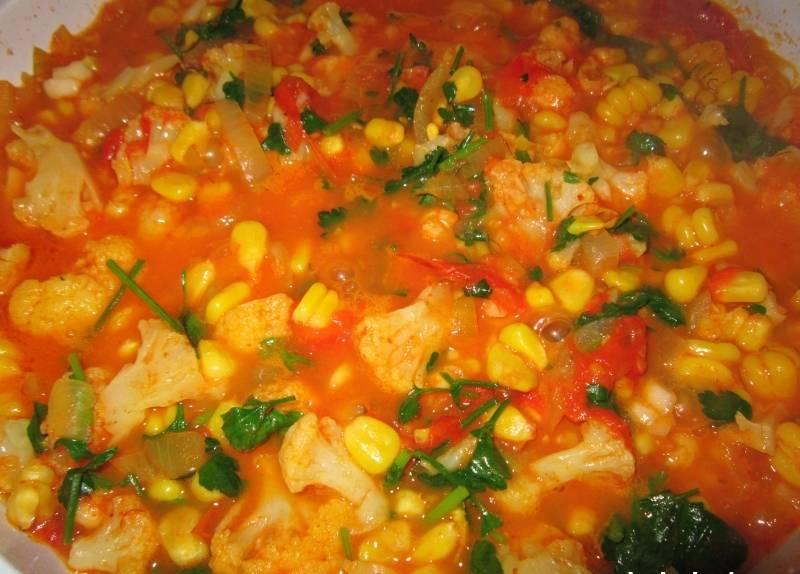 4. Пока жарятся помидоры с луком и морковью, отвариваем в слегка подсоленной воде соцветия цветной капусты. Варить нужно не долго - не более 2 минут. После этого отправляем капусту к помидорам, добавляем чеснок, кукурузу и заливаем стаканом воды. По вкусу можно добавить зелень петрушки и специи. Тушим до готовности овощей.