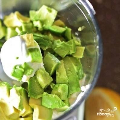 Снимаем кожицу с авокадо, нарезаем плод хаотичными небольшими кусочками, загружаем их в чашу блендера.