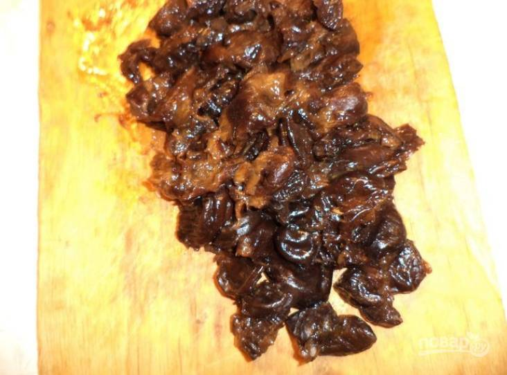 2.Чернослив выложите в миску, залейте его кипятком и отставьте в сторону на 15 минут, затем слейте воду и нарежьте плоды небольшими кусочками.