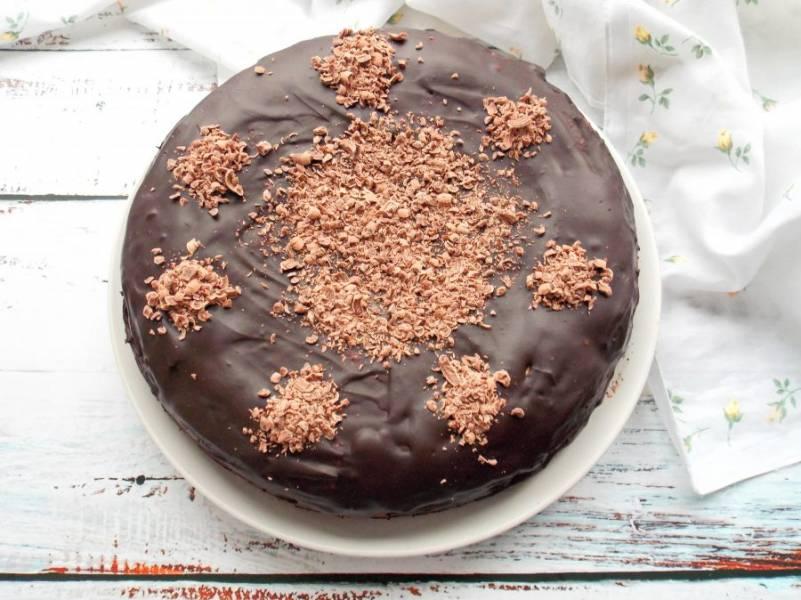 Оставшийся шоколад натрите на крупной терке и пока не застыл верхний шоколадный слой, украсьте торт.