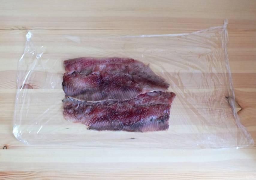 Селедку разделайте на 2 филе. На рабочей поверхности расстелите пищевую пленку. Выложите на нее рыбу, внахлест. Одна часть филе соприкасается хвостовой частью с широкой частью второго филе. Отбейте слегка молоточком.