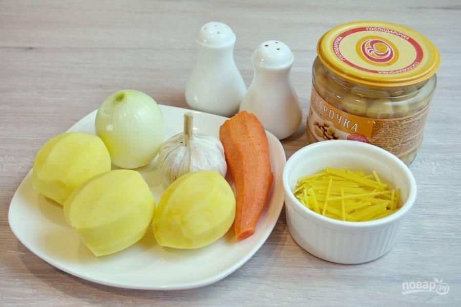 Для приготовления супа возьмите необходимые продукты: картофель, морковь, лук, чеснок, фасоль консервированную, куркуму, лапшу готовую или домашнюю, растительное масло, специи.