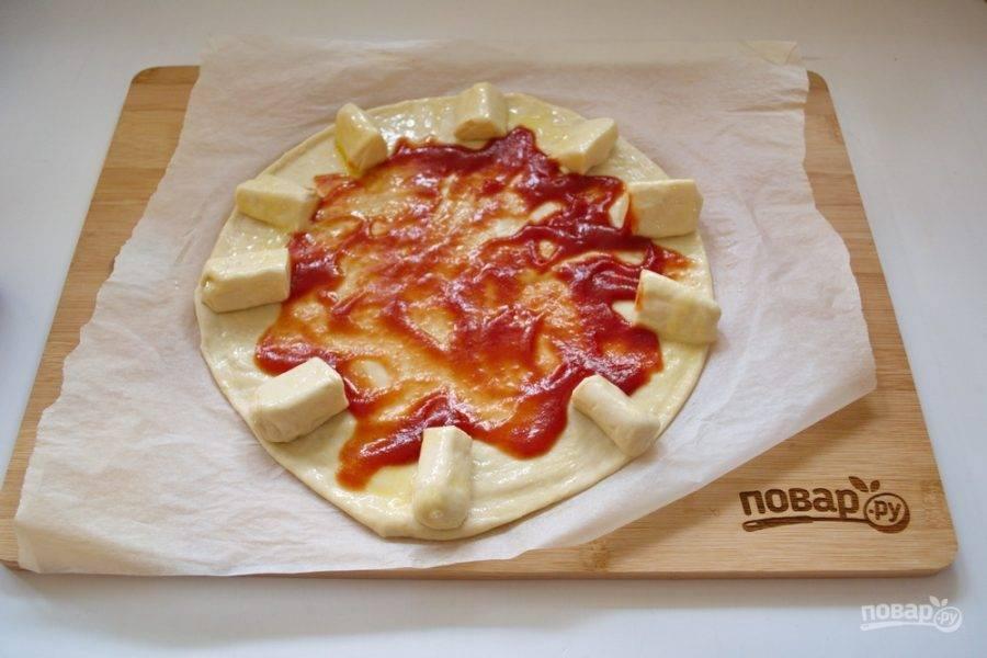 Края пиццы вместе с булочками смажьте взбитым яйцом. Серединку теста смажьте томатным соусом. Можно использовать кетчуп.