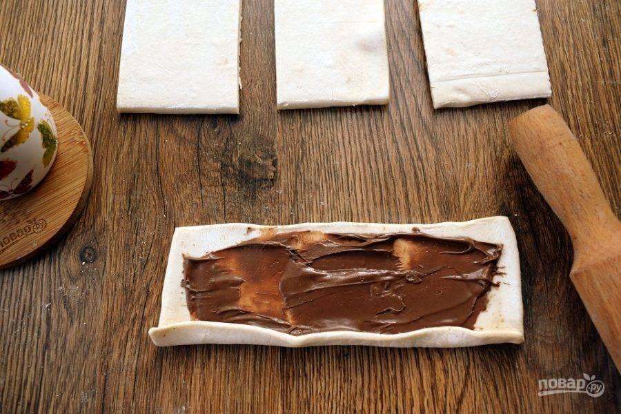 Каждый раскатайте в одном направлении. Намажьте шоколадно-ореховую пасту (1 ч.л.) на заготовку теста, оставляя немного места по краям.