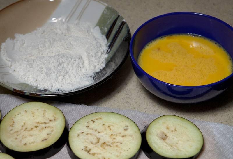 3. В небольшой мисочке взбить яйца. В другую насыпать муку. Также в рецепт приготовления жареных баклажанов с уксусом и чесноком можно использовать панировочные сухари для более хрустящей корочки.