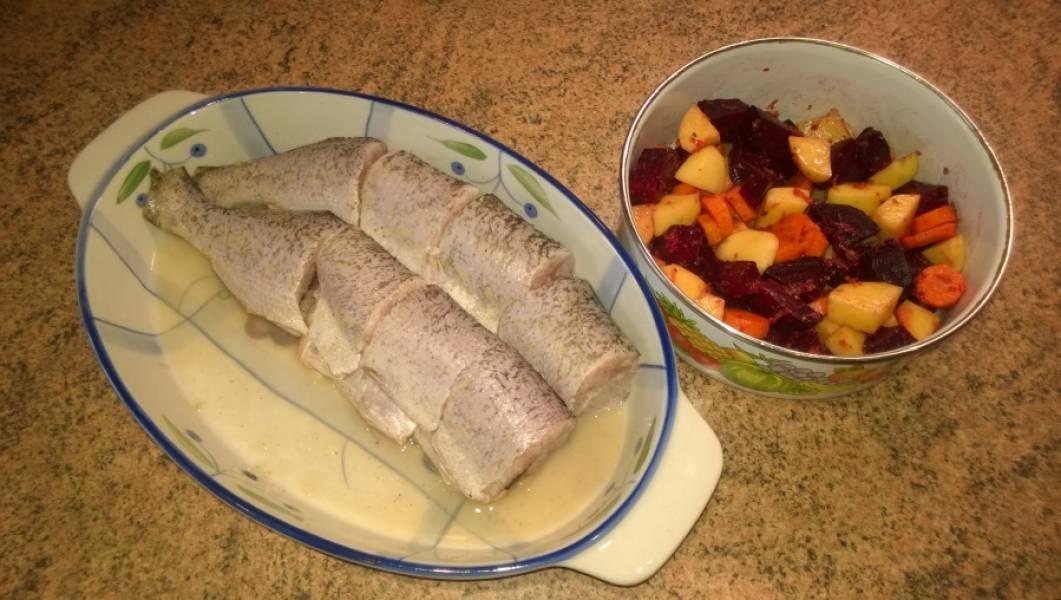 2. Рыбу разрежьте на порционные куски, посолите, поперчите. Выжьмите сок из лимона, замаринуйте в нем рыбу. Оставьте на 20 минут. За это время некрупно, произвольно порежьте овощи, кроме лука и чеснока. Посолите, посыпьте специями для овощей, натрите туда же чеснок на мелкой овощной терке. Все перемешайте, дайте постоять 10 минут.