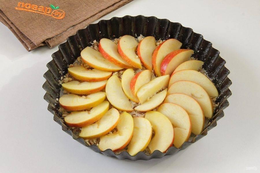 Оставшееся яблоко разрежьте пополам, удалите сердцевину и нарежьте дольками. Выложите ровным слоем на ореховую крошку.