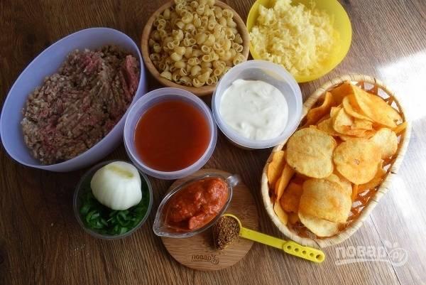 Подготовьте необходимые продукты. Сыр натрите  на мелкой терке. Лук очистите. Макароны поставьте отвариваться в кипящей подсоленной воде.