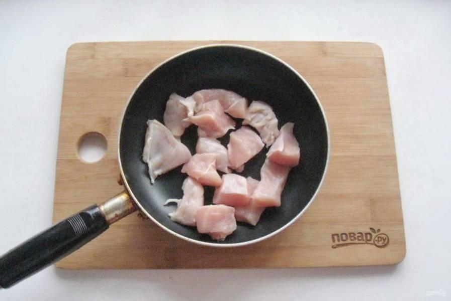 Куриное филе помойте, нарежьте кубиками и выложите в сковороду с подсолнечным маслом.