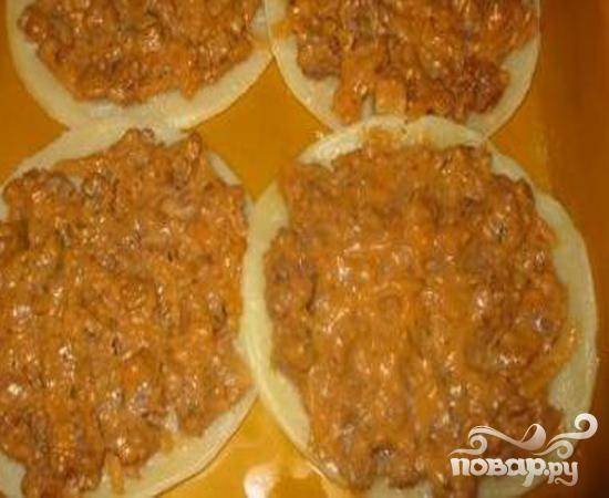 3.Из раскатанного теста вырезаем лепешки круглой формы. У нас получается порционная лазанья.  Тесто выкладываем в форму для запекания и раскладываем на него половину нашего мясного фарша.