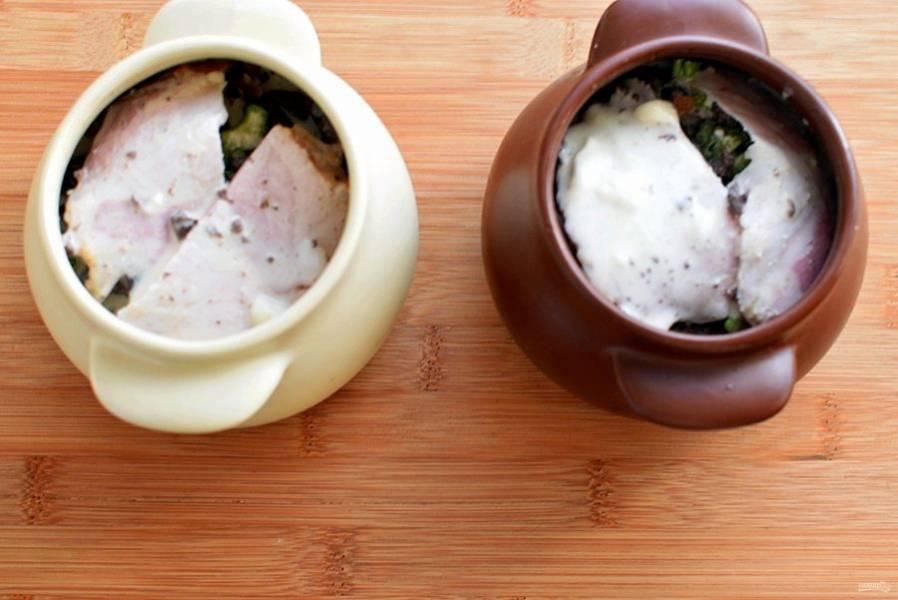 Уложите сверху тонкие ломтики грудинки или бекона. Сметану размешайте с солью и горячей водой и равномерно залейте горшочки. Посыпьте тимьяном, накройте крышечками и запекайте в духовке, разогретой до 180 градусов, около получаса.