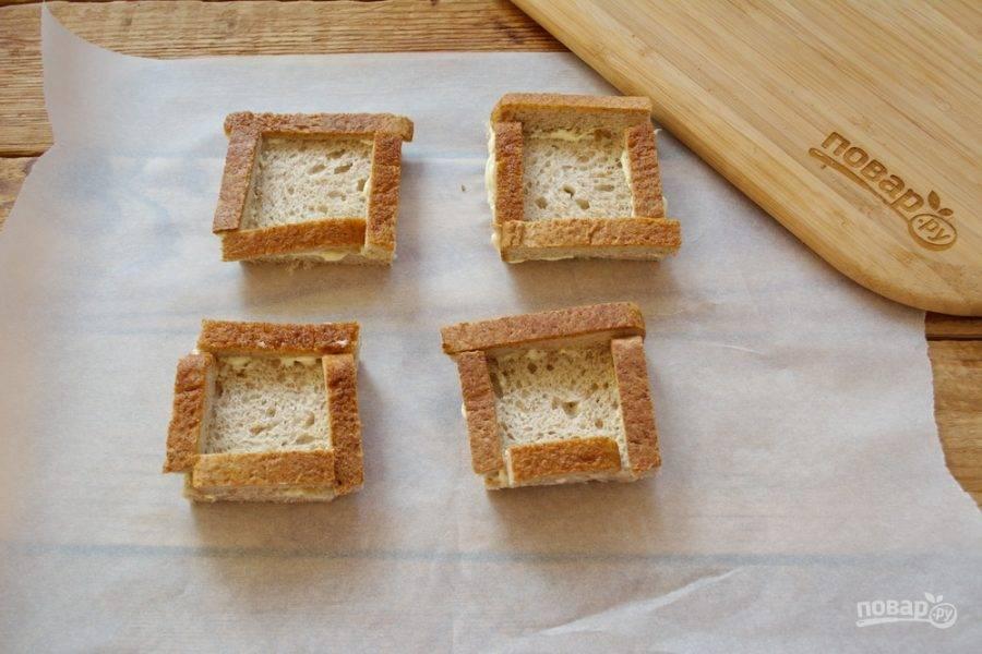 Сразу перенесите тосты на бумагу для выпечки или на противень. Так легче будет переместить тосты в духовку для запекания.