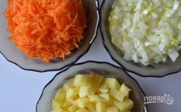 1. Для начала очистите все овощи. Картофель нарежьте небольшими кубиками, измельчите лук и натрите на терке морковь.