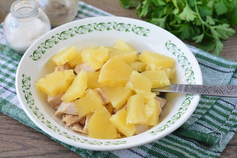 Кольца ананасов нарежьте средними кусочками и добавьте в салат.