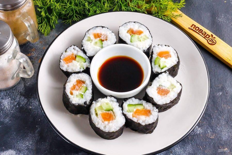 Разрежьте его пополам, а затем каждую половинку разрежьте еще 1-2 раза, в зависимости от толщины роллов, ее выбирайте по своему вкусу. Выложите роллы на тарелку вместе с соевым соусом.
