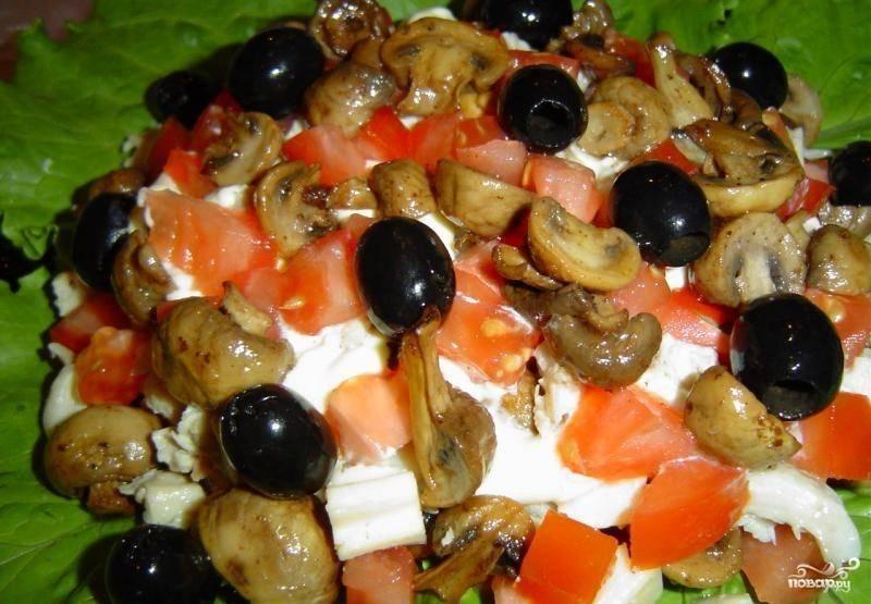 6. Теперь выложите оставшиеся помидоры, сыр и грибы слоями. Сверху положите целые маслины. Салат «Майский» готов!