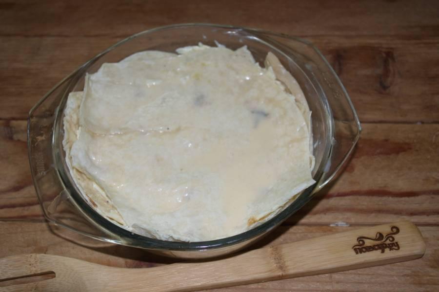 Поверх сыра снова выложите кусочки лаваша, а потом снова сыр — и так, пока все продукты не закончатся.