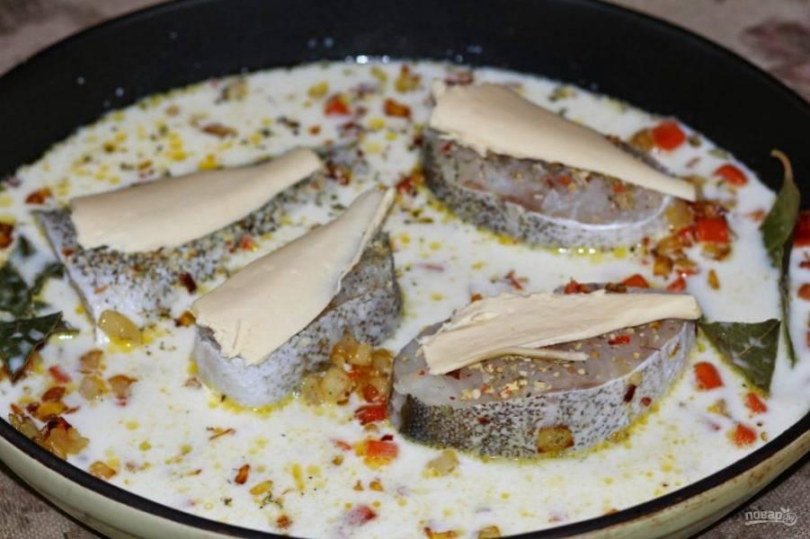 В форму для запекания выложите стейки трески, обжаренные овощи, добавьте лавровый лист, залейте все горячим молоком. Затем присыпьте все приправой для рыбы, а на каждый стейк положите по кусочку сливочного масла.