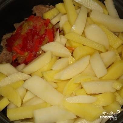 К обжаривающемуся мясу добавить лук и чеснок. Следом добавить все нарезанные овощи.