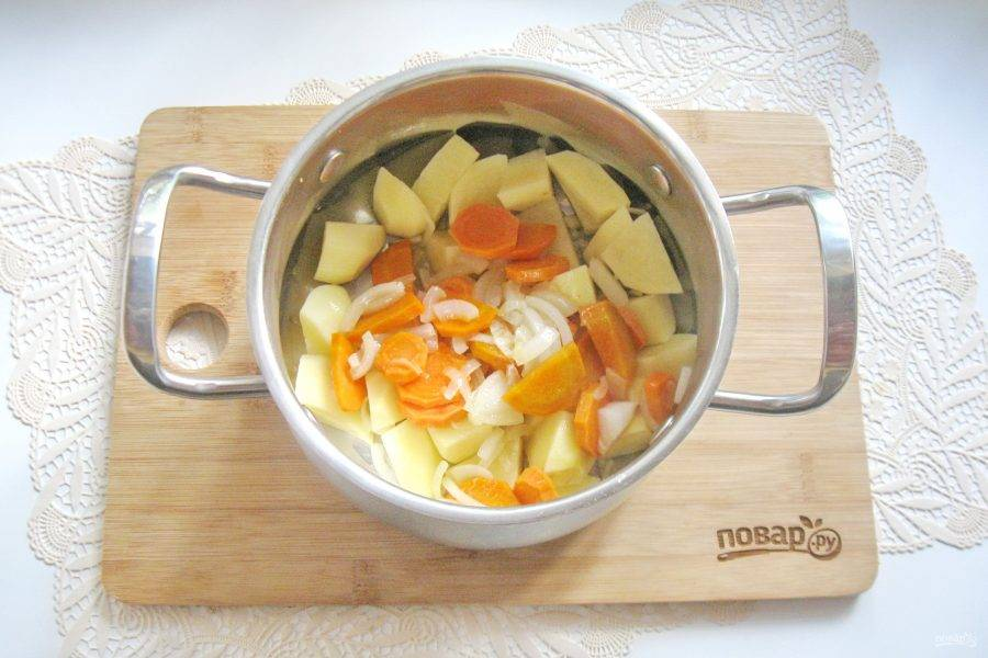 Выложите морковь с луком в кастрюлю с картофелем.