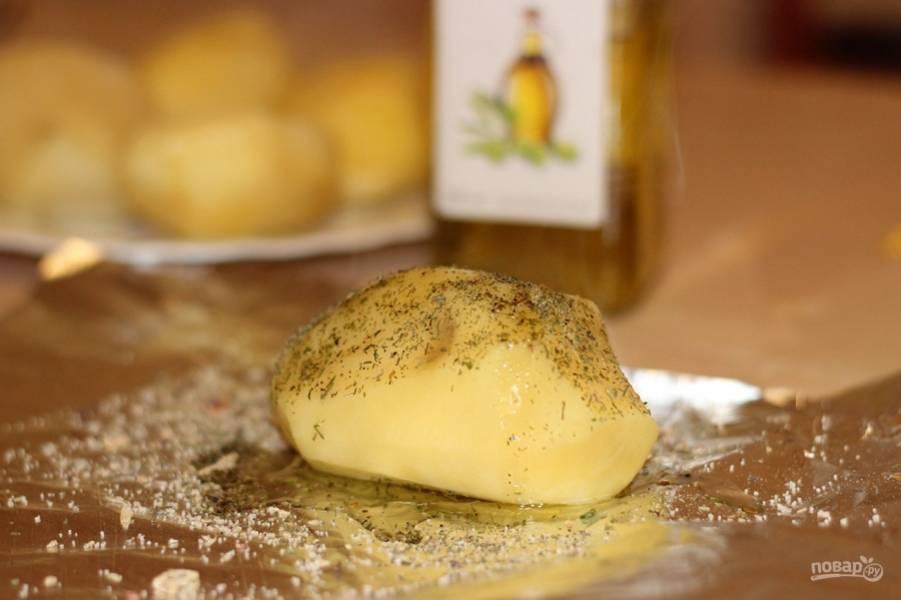 Затем картошку посыпьте приправами на свой вкус, сбрызните оливковым маслом и заверните в фольгу.