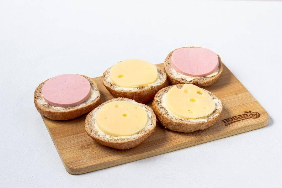 Колбасу и сыр нарежьте пластинами, с помощью небольшого кулинарного кольца вырежьте кружочки по размеру хлебцов. Разложите колбасу и сыр на хлеб.