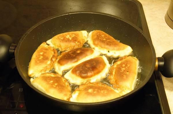 5. Разогреть небольшое количество растительного масла на сковороде. Жарить пирожки с солеными огурцами в домашних условиях с двух сторон до аппетитной румяной корочки.