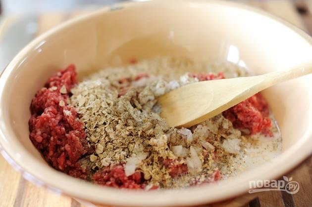 2. Добавьте к фаршу овсянку быстрого приготовления, молоко, измельченную половину лука, соль и перец. Перемешайте фарш до получения однородной смеси.