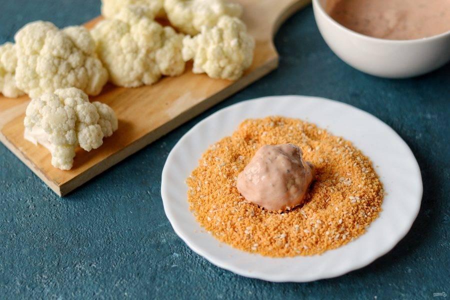 Насыпьте панировочные сухари в тарелку. Обмакните соцветие цветной капусты в кляр, затем обваляйте в панировке.
