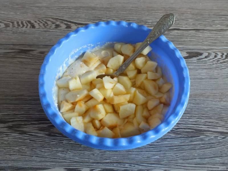 Нарезанные яблоки добавьте в тесто и перемешайте ложкой.