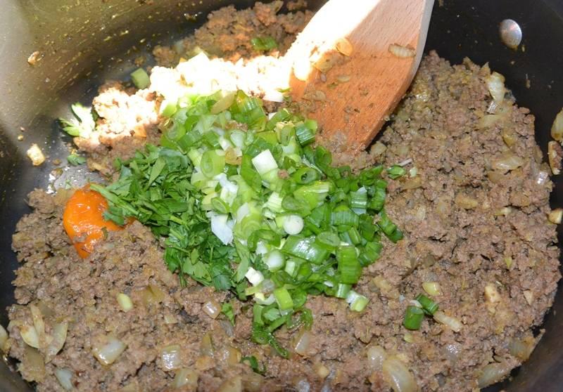 Ставим на огонь сковороду, разогреваем в ней пару ложек растительного масла, обжариваем на масле до золотистого цвета нарезанный лук и измельченный чеснок. Далее выкладываем на сковороду говяжий фарш, продолжаем все обжаривать, а когда фарш зарумянится, добавляем в начинку острый перец (целиком), специи и соль, вливаем полстакана воды. Тушим фарш на медленном огне 10 минут, затем смешиваем его с панировочными сухарями и готовим все еще 5 минут. После этого снимаем сковороду с огня, добавляем в начинку измельченную зелень.