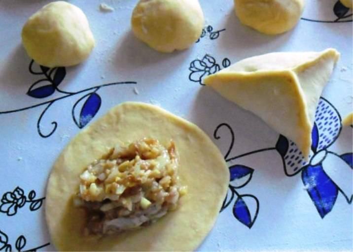 Тесто разделите на небольшие шарики, раскатайте их в лепешки, на каждый выложите начинку. Слепите треугольный пирожок, смажьте его яйцом и отправьте на противень. Выпекайте в разогретой до 200 градусов духовке 25-30 минут. На стол подавайте в горячем виде.