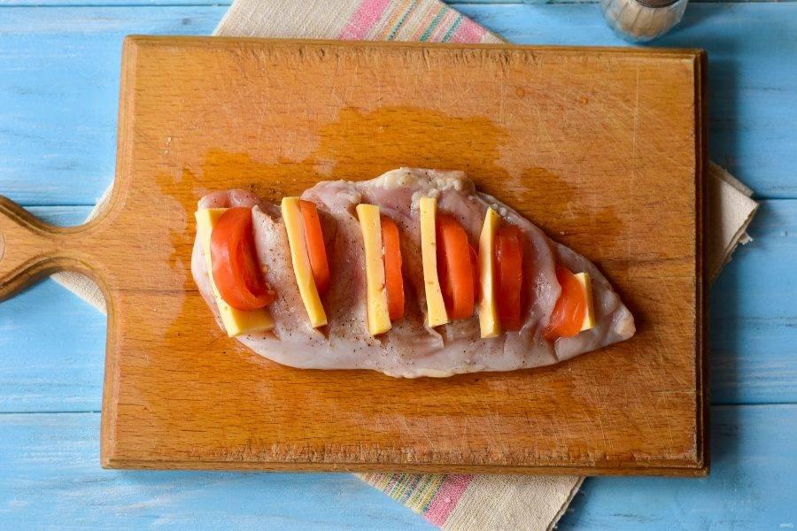 В каждый разрез вставьте по кусочку помидора и твердого сыра.