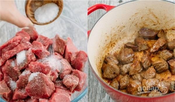 1. В кастрюлю налейте немного растительного масла, поставьте её на огонь. Говядину вымойте, обсушите и нарежьте среднего размера кусочками. Добавьте соль, перемешайте. Выложите в кастрюлю (сначала половину, чтобы лучше прожаривалось) и обжарьте на среднем огне до румяной корочки. Снимите мясо, пока отложите его в сторону.