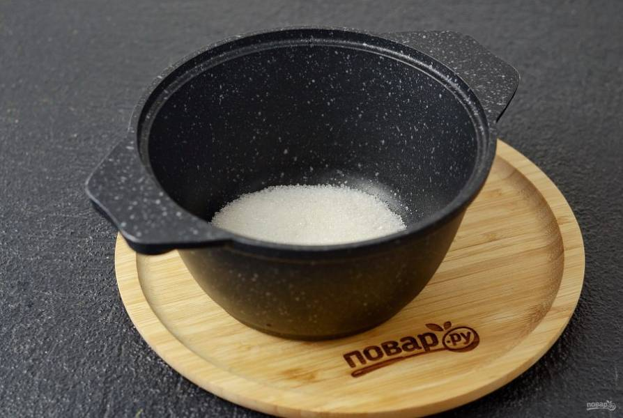 В кастрюле с толстым дном соедините сахар и воду. Уварите до состояния густой карамели коричневого цвета. Постоянно помешивайте.