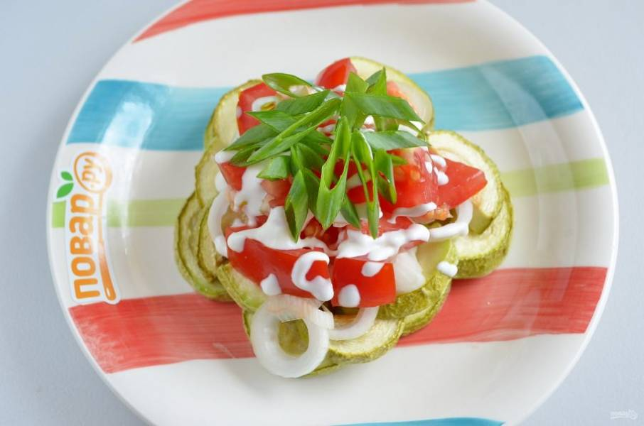 Соберите салат порционно: сначала – кабачки, далее – лук, помидоры. Сверху – майонезная сеточка и лук зеленый. Приятного аппетита!