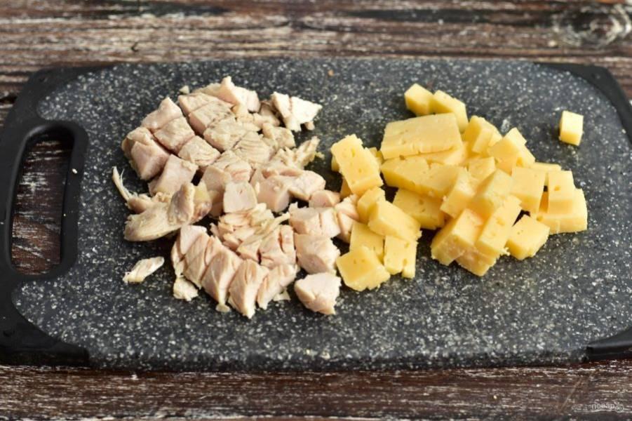 Нарежьте вареное куриное филе и твердый сыр.