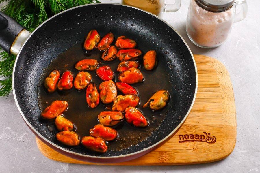 Прогрейте на сковороде растительное масло и обжарьте в нем мидии примерно 2-3 минуты. Затем влейте туда соевый соус и потушите мидии около 3 минут. Выключите нагрев.